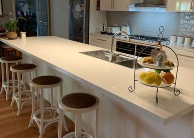 refurbished white kitchen, showing stools, bench top, appliances, stove top