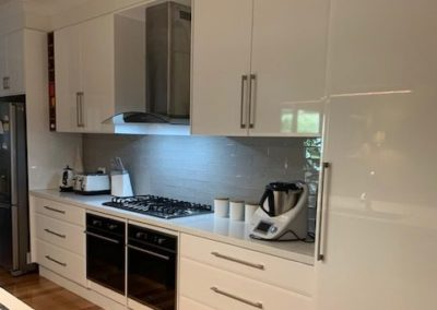 refurbished white kitchen, showing all cupboards, draws, appliances, ovens, stove top and range hood