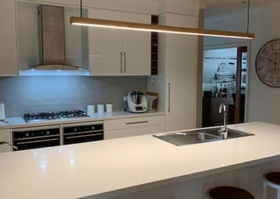 refurbished white kitchen, showing stools, sink, range hood, stove top, bench space and cupboards