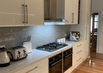 refurbished white kitchen, picture taken from a diagonal so that the entire cooking space eg. range hood, stove, storage, pantry are all included
